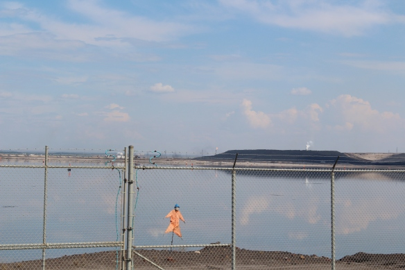 A scarecrow stands guard to prevent birds from landing on an oilsands tailings pond.
